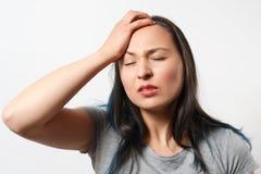 Unga flickan griper hennes huvud med hennes hand och visar en sträng huvudvärk P? vitbakgrund royaltyfria foton