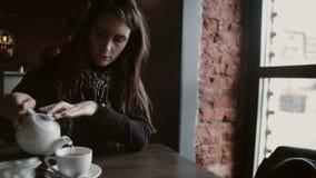 Unga flickan häller te från en kokkärl in i ett rånasammanträde i modernt kafé Arkivbild