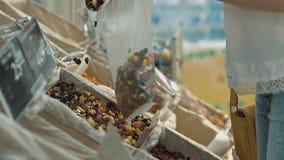 Unga flickan häller torkat - frukt in i en packe stock video
