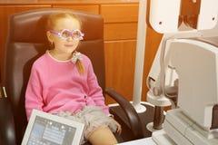 Unga flickan har ögonexamen att utföras av optiker, optometrikern eller ögondoktorn fotografering för bildbyråer