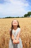 Unga flickan har gyckel i vetefält Arkivbilder