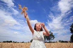 Unga flickan har gyckel i vetefält Royaltyfri Fotografi