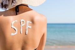 Unga flickan har spf-ord p? hennes baksida som g?ras av solkr?m p? stranden Begrepp f?r solskyddsfaktor arkivbild