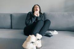 Unga flickan hemma på soffan i varm stucken tröja med en näsduk, nyser Influensa och kall säsong arkivbilder