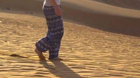Unga flickan i asiatiska flåsanden promenerar sanden av den röda öknen i Mui Ne, Vietnam stock video