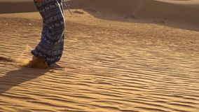 Unga flickan i asiatiska flåsanden promenerar sanden av den röda öknen i Mui Ne, Vietnam lager videofilmer