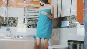 Unga flickan i blå handduk går i vattenkran för badrumöppningsvatten bada att ta arkivfilmer