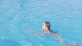 Unga flickan i den vita bikinin simmar i simbassäng Den tonåriga flickan tycker om sommarsemester på en solig dag i vatten av uto lager videofilmer