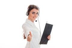 Unga flickan i den vita skjortan och hörlurar med mikrofon som rymmer en minnestavla för legitimationshandlingar och shower, gör  Royaltyfri Foto