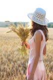 Unga flickan i det hållande vetet för hatten och för rosa färgklänningen gå i ax i hennes hand arkivfoton