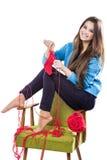 Unga flickan i en blå tröja sitter på en stol med ett rött garnnystan och att sticka en halsduk och en Spitz leenden Vit bakgrund Arkivbilder