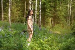 Unga flickan i en Forest Park aktivitet dansar bland blommor och björkträd royaltyfria foton