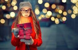 Unga flickan i en hatt och tumvanten öppnar en gåvaask på gatan Royaltyfri Fotografi