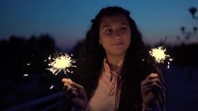 Unga flickan i en klänning står med fyrverkerier i händerna på en bakgrund av en nattstad som har ett bra lynne långsam rörelse stock video