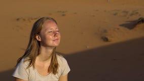 Unga flickan i en lotusblomma poserar möter gryningen i den röda öknen lager videofilmer