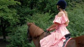 Unga flickan i en skyddande hjälm och en rosa klänning rider en brun häst på bakgrunden av träd och lövverk 4K video 4K arkivfilmer