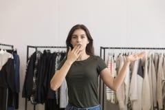 Unga flickan i ett bekläda lager täcker hennes mun med hennes hand royaltyfri fotografi