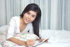 Unga flickan i ett rum ligger ner på en säng- och handstildagbok arkivbild