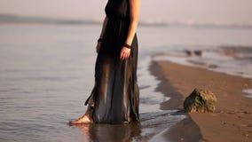 Unga flickan i ett svart klänningsammanträde på en vagga vid floden får övre och går på vattnet lager videofilmer