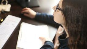 Unga flickan i exponeringsglas som sitter på en dator, arbetar arkivfilmer