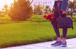 Unga flickan i jeans med buketten av den tulpanblommor och påsen går parkerar in Royaltyfri Foto