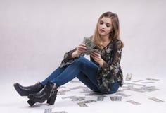 Unga flickan i jeans sitter med finansiella dollar Royaltyfri Bild