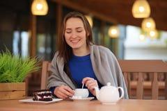 Unga flickan i kafé sitter och dricker te fotografering för bildbyråer