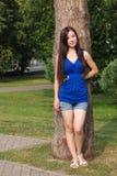Unga flickan i kortslutningar lutade mot ett träd i parkera Royaltyfria Foton
