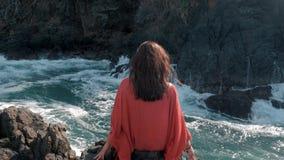 Unga flickan i röd klänning sitta nära att slå för stormvågor vaggar unga flickan som ut ser till havet, vågavbrott stock video