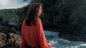 Unga flickan i röd klänning sitta nära att slå för stormvågor vaggar unga flickan som ut ser till havet, vågavbrott arkivfilmer