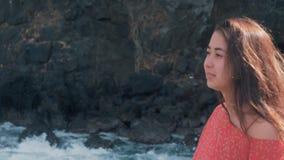 Unga flickan i rött klänninganseende nära att slå för stormvågor vaggar unga flickan som ut ser till havet, vågavbrott lager videofilmer