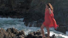 Unga flickan i rött klänninganseende nära att slå för stormvågor vaggar unga flickan som ut ser till havet, vågavbrott arkivfilmer