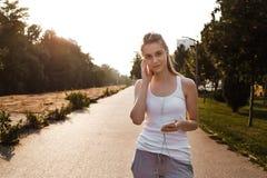 Unga flickan i sportswearen som joggar på vägen fotografering för bildbyråer