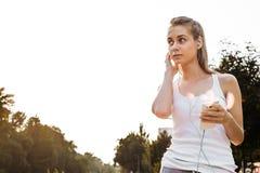Unga flickan i sportswearen som joggar på vägen royaltyfri foto