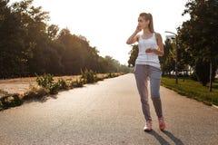 Unga flickan i sportswearen som joggar på vägen royaltyfria bilder