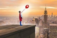 Unga flickan i superherodräkt som förbiser staden Arkivfoton