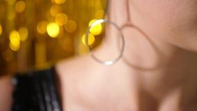 Unga flickan i svart klänning av våg står på bakgrunden av guld- glitter lager videofilmer