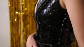 Unga flickan i svart klänning av våg står på bakgrunden av guld- glitter stock video