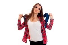 Unga flickan i t-skjorta och plädskjorta håller en tung portfölj på hans skuldror och ser upp arkivfoton