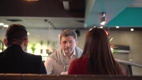 Unga flickan introducerar hennes pojkvän till hennes fader för förbindelse i ett kafé stock video
