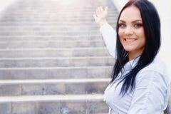 Unga flickan inviterar för att klättra upp stegen arkivbilder