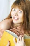 Unga flickan jublar läst in en bok Fotografering för Bildbyråer