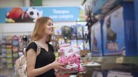 Unga flickan köper rullskridskor lager videofilmer