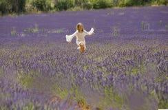 Unga flickan kör i fält av lavendel, Provence Royaltyfri Fotografi