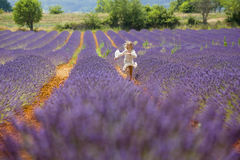 Unga flickan kör och hoppar i ett purpurfärgat fält av lavendel Arkivfoto