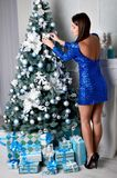 Unga flickan klär upp julgranen arkivfoton