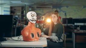 Unga flickan kontrollerar en robot på en tabell Futuristisk humanoid och tekniker stock video