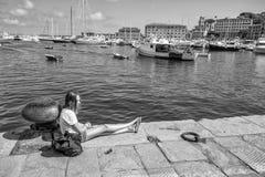 Unga flickan kopplar av i porten av Santa Margherita Ligure, det Genoa Genova landskapet, Ligurian Riviera, Italien arkivbilder