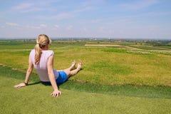 Unga flickan kopplar av på gräs royaltyfria foton
