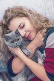 Unga flickan kramar den skotska katten royaltyfri bild